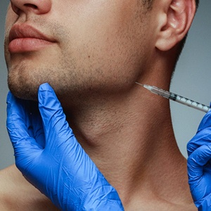 cosmetic dentist in Lakewood injecting BOTOX into a patient's chin