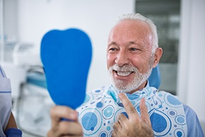Older man smiling while looking in dental mirror