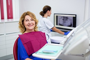 Woman in blue smiling in dental chair